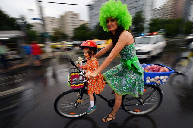Mã e filha num passeio de bicicletapelas ruas de Bucareste, Roménia, durante o evento 'Skirtbike' a 10 de Outubro de 2013 (Foto créditos: Daniel Mihailescu / AFP / Getty Images)