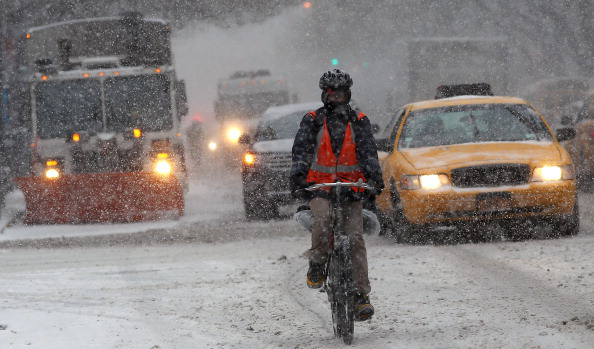 NEW YORK, NY - JANUARY 21:  A man rides a bicycle in Manhattan during a snowstorm that is moving through the Northeast on January 21, 2014 in New York City. Along with dropping arctic tempertures the storm is expected to bring three to five inches by nightfall, with another four to six inches falling overnight.  (Photo by Spencer Platt/Getty Images)